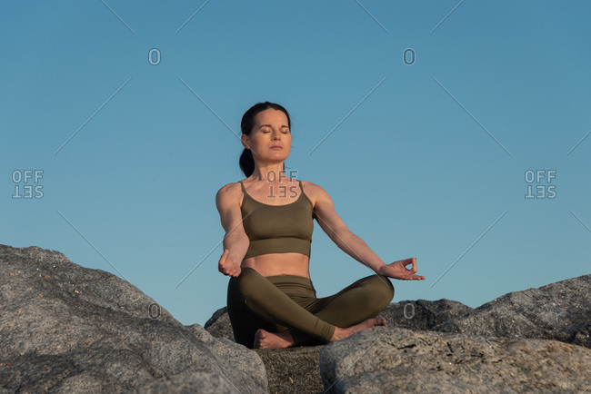 Low angle of young female in activewear sitting in lotus pose with mudra gesture and practicing yoga meditation on stones against clear blue sky
