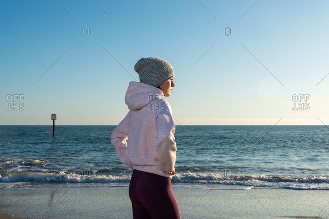 Side view of slim female in activewear and knitted hat standing on sandy shore near sea water and enjoying sunny weather while relaxing after fitness workout