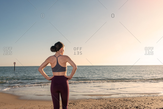 Back view of slim female in activewear standing on sandy shore near sea water and enjoying sunny weather while relaxing after fitness workout