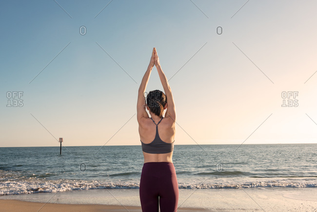 Back view of unrecognizable female in activewear standing in Mountain pose with arms up while practicing yoga on sandy beach near waving sea