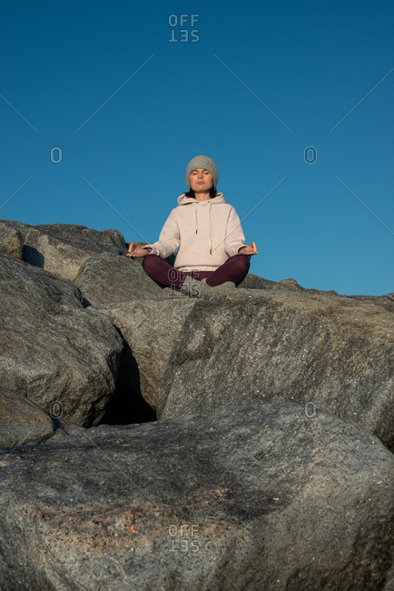Young female in warm activewear and knitted hat meditating with mudra hand gesture while sitting on rock against blue sky