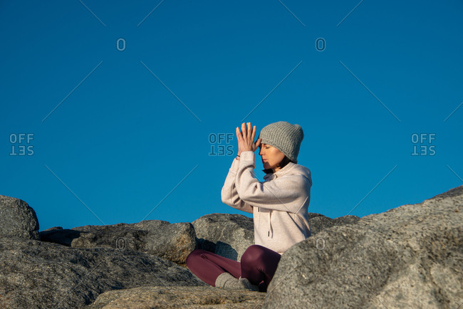 Side view of young female in warm activewear and knitted hat meditating with praying hands while sitting on rock against blue sky