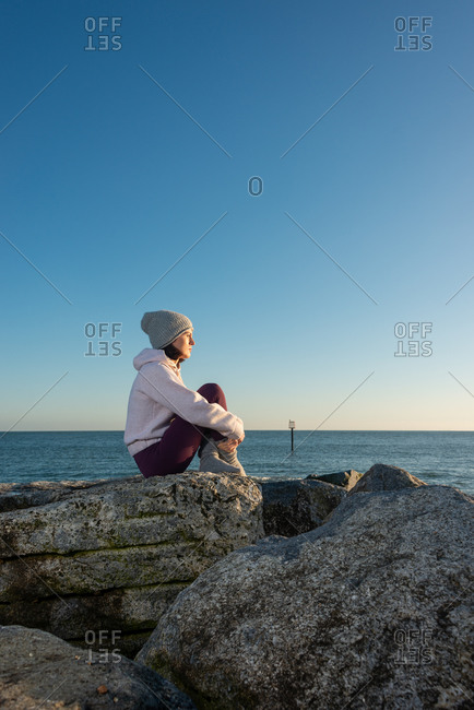 Side view of calm pensive young female in warm activewear sitting on rocky seashore and looking away while relaxing alone in sunny day