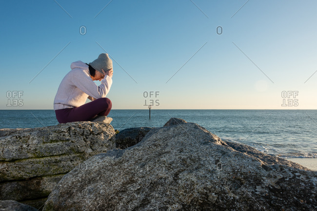 Side view of depressed lonely young female in casual warm clothes thinking about problem while sitting on stone near sea