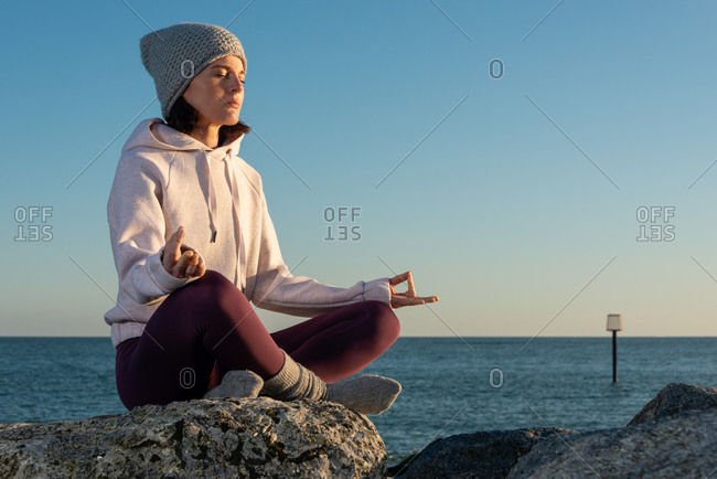 Side view of young female in warm activewear and knitted hat meditating with mudra hand gesture while sitting on rock against blue sky