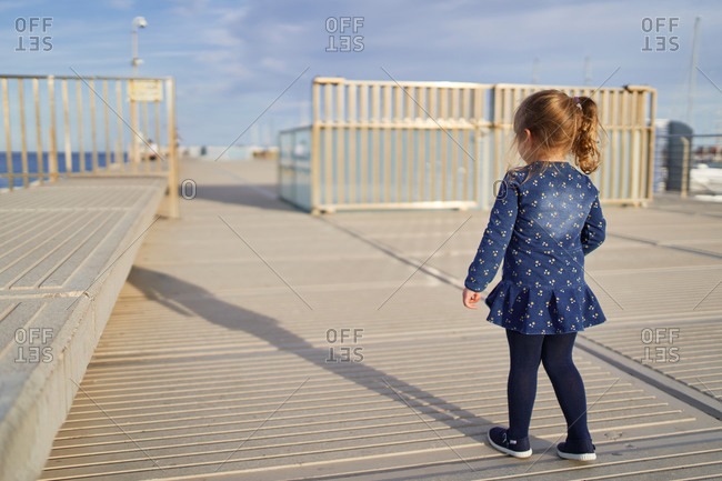 Back view of adorable cheerful little girl in blue dress with toy on hand having fun on paved walkway in summer day