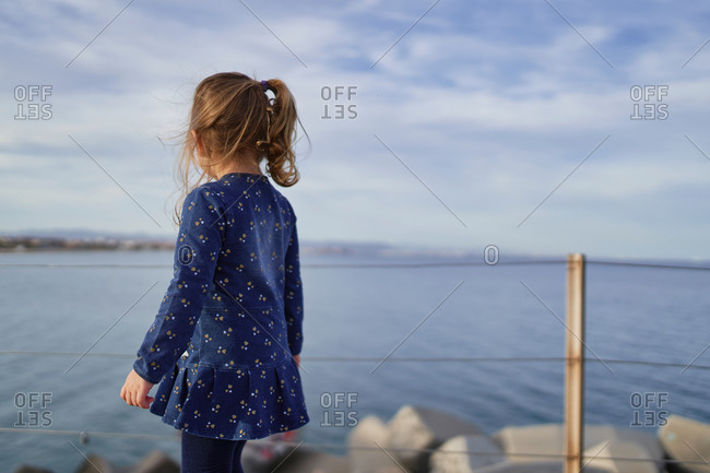Back view of unrecognizable little child in dress standing on promenade and enjoying view of sea in summer