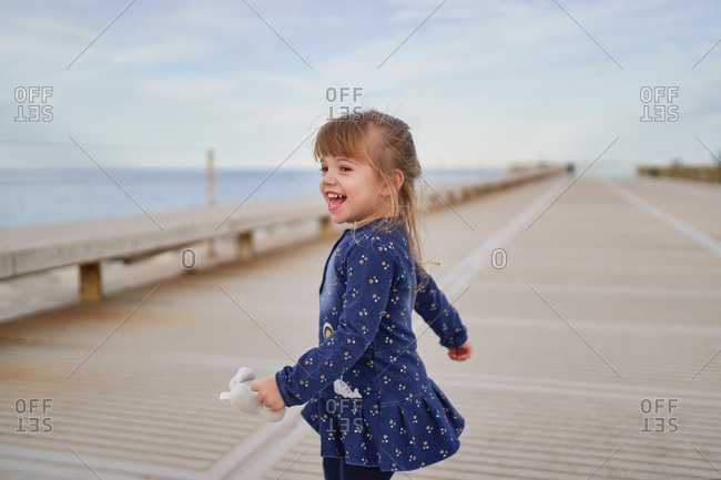 Side view of adorable cheerful little girl in blue dress with toy on hand having fun on paved walkway in summer day
