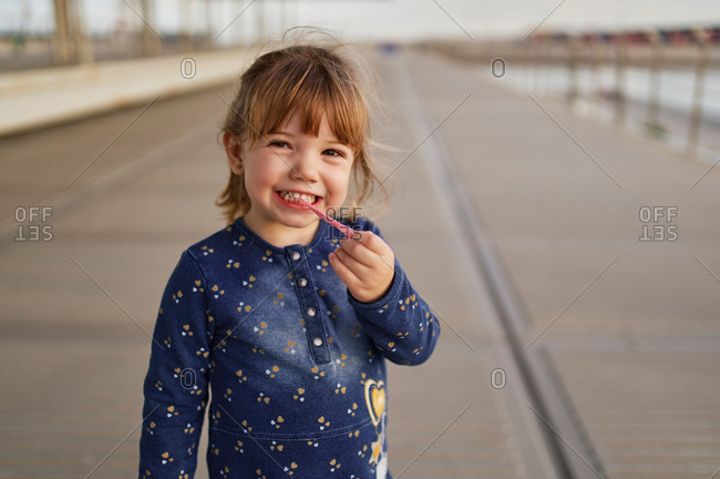 Cute little kid standing on wooden promenade and playing with pink bubble gum