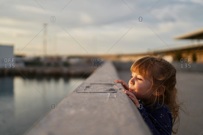 Side view of curious little girl in casual wear standing near railing on urban bridge and looking away in summer evening