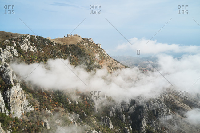 Drone view of picturesque landscape of rocky mountains with green slopes covered by thick white clouds in sunny autumn day