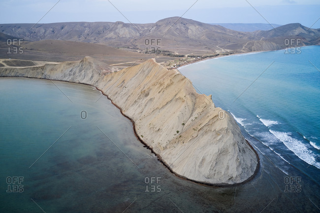 Spectacular drone view of hilly coastline of Crimean peninsula with rough rocky cape washed by blue sea water