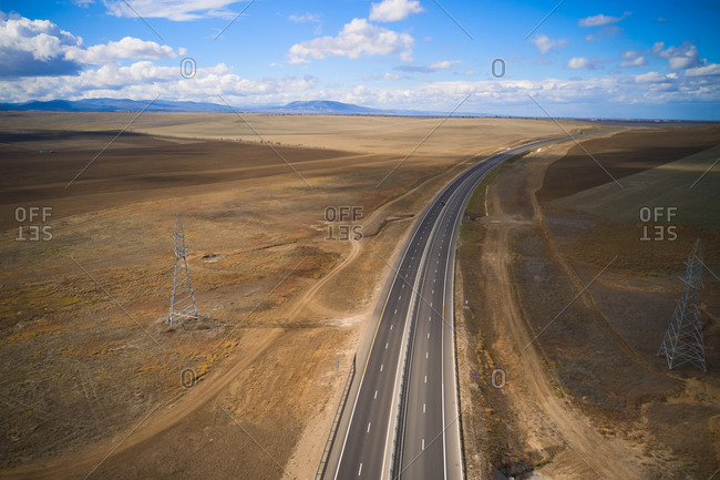 From above drone view of curvy asphalt roadway through desert grassy land in mountainous region in sunny autumn day