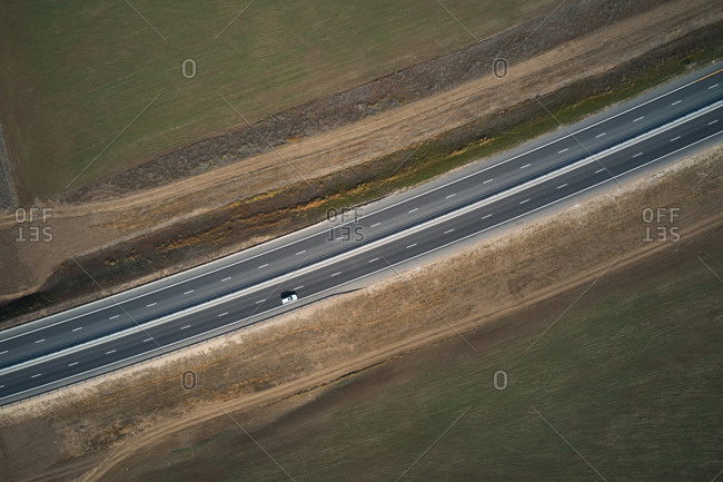 From above drone view of curvy asphalt roadway with lonely car running through desert grassy land in mountainous region in sunny autumn day