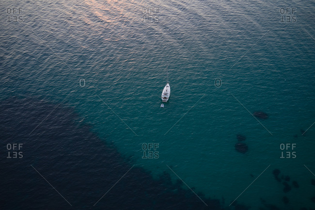 From above drone view of lonely modern yacht floating on rippling surface of calm sea water
