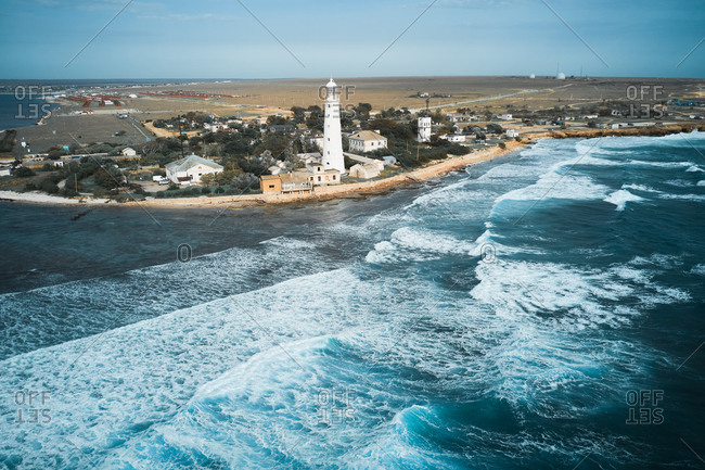 From above drone view of white lighthouse tower and small settlement located on rocky coast washed by foamy sea waves