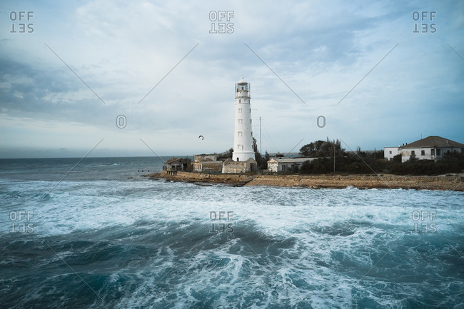White lighthouse tower and small settlement located on rocky coast washed by foamy sea waves