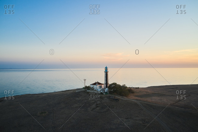 Spectacular drone view of beacon located on hill on background of calm sea and sundown sky
