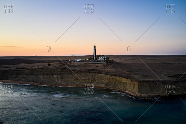 Tower of white beacon located on coast near waving sea under overcast sky