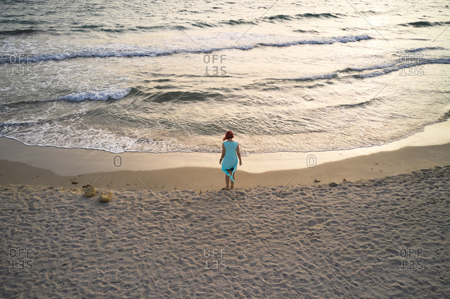 Full body back view of unrecognizable female traveler standing barefoot on empty sandy beach near waving sea and enjoying fresh breeze during summer holidays