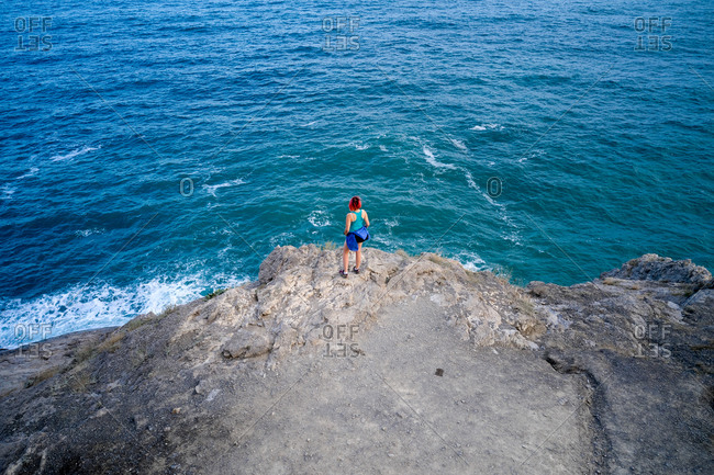 From above of anonymous female tourist standing on rock and enjoying view of turquoise sea during summer vacation