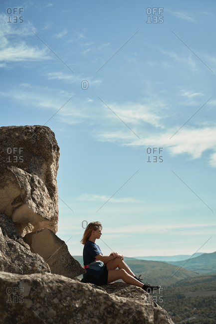 Side view of female hiker relaxing on rocky hill and enjoying majestic scenery of mountains in summer