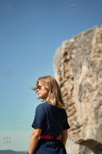 Back view of female tourist standing in highlands and looking away on background of blue sky and rocky cliff