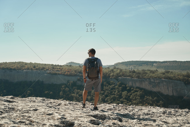 Back view of traveling man standing with backpack on rough hill and enjoying view of highland valley during summer holiday