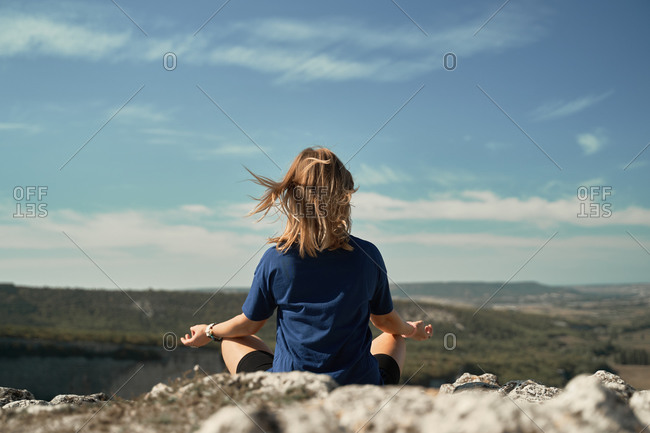 Back view of unrecognizable female traveler sitting in Lotus pose on hill and meditating with mudra hands while doing yoga in highlands during vacation