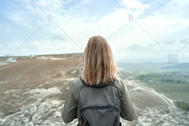 Back view of anonymous female backpacker standing on hill and admiring magnificent scenery of mountains during trip