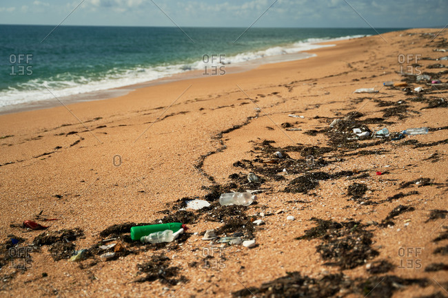 Sandy shoreline with trash and garbage scattered near blue sea on sunny day showing concept of environmental pollution