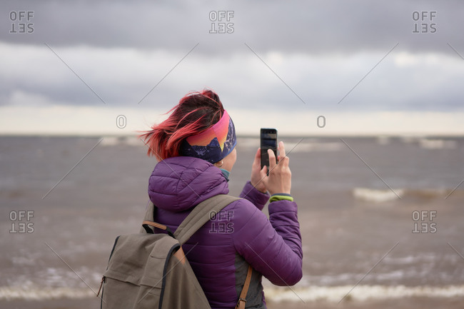 Back view of unrecognizable female traveler with backpack and in warm clothes standing on shore and taking picture of waving sea on overcast day in Sestroretsk