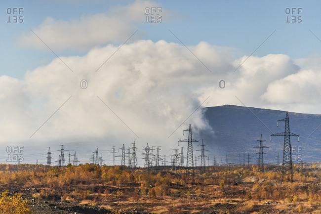 Scenic landscape of power lines and pylons located in field in autumn on sunny day in highland area