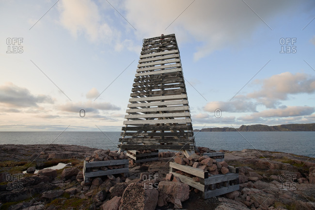 Scenic view of beacon made of wooden pallets located on rocky seashore at sunset