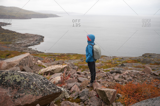 Side view of female hiker in warm clothes and with backpack trekking in rocky terrain on cloudy weather near sea
