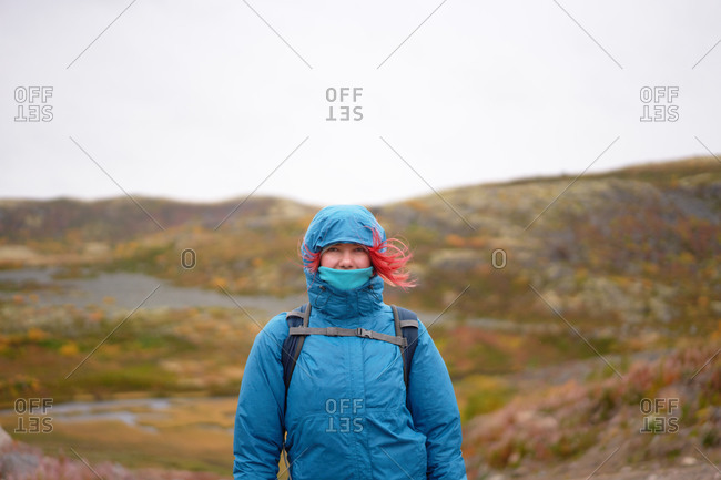 Female hiker in warm clothes and with backpack trekking in rocky terrain on cloudy weather near sea and looking at camera