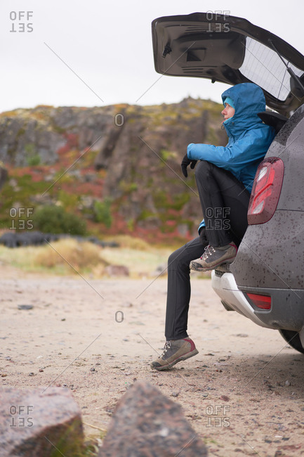 Female traveler in outerwear sitting in car trunk and looking away