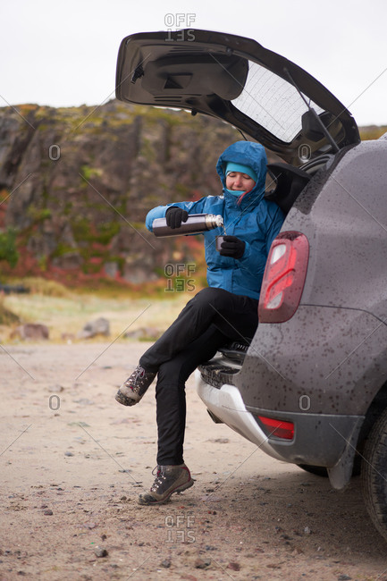 Side view of carefree female traveler in outerwear sitting in car trunk and enjoying hot drink from thermos cup