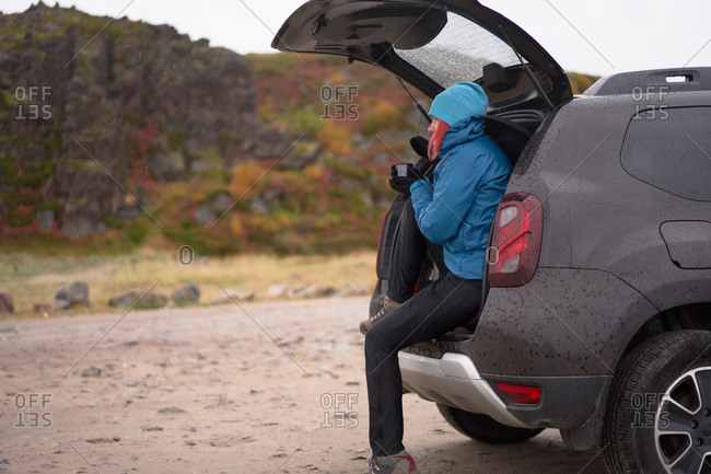 Side view of carefree female traveler in outerwear sitting in car trunk and enjoying hot drink from thermos cup while looking away
