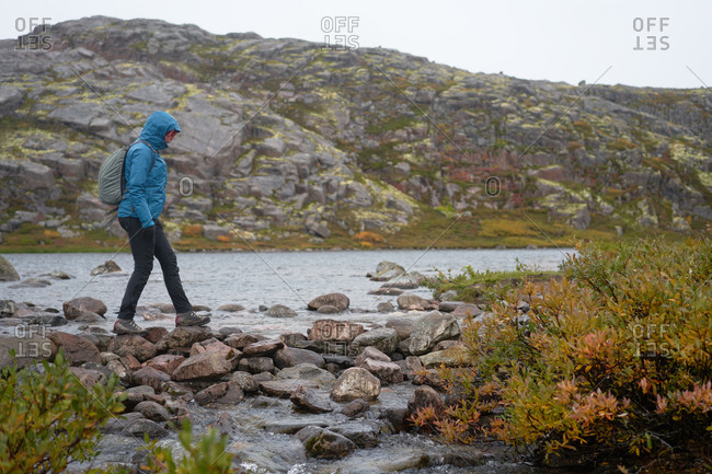 Side view of female explorer in warm clothes crossing river while walking along wet stones in highland area during travel in autumn
