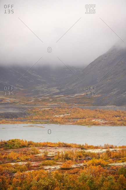 Breathtaking scenery of calm lake and autumn forest in highland area on misty day