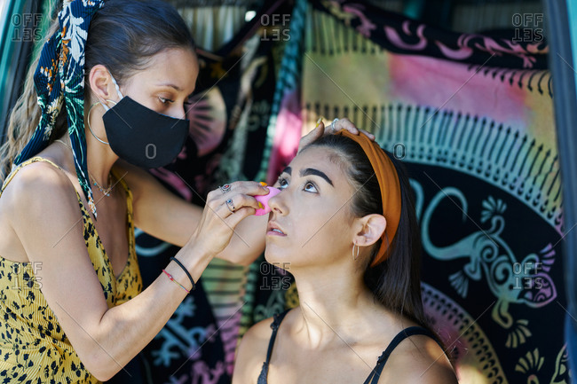 Female makeup artist applying eyebrow pencil and doing stylish makeup for woman sitting in van