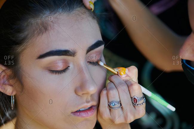 Female makeup artist applying eyeshadow and doing stylish makeup for woman sitting in van