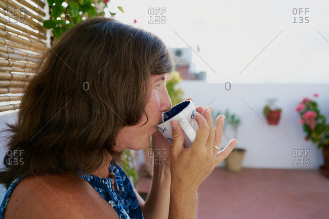 Side view of adult female in casual wear enjoying hot coffee while relaxing on terrace of house in summer day