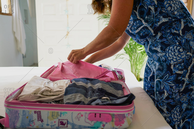 Side view of crop anonymous female packing clothes into colorful suitcase while preparing for trip at home