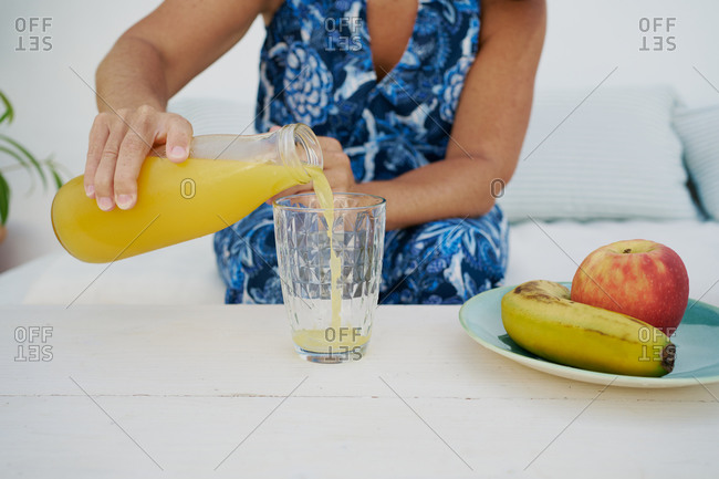 Crop unrecognizable female in summer dress pouring fresh orange juice from bottle into glass placed on table with fruits at home