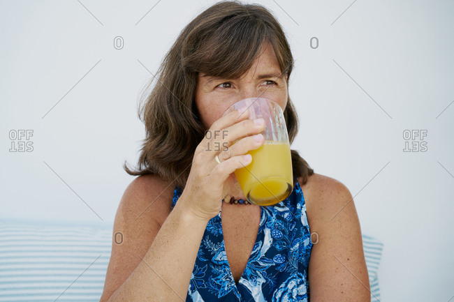 Female in summer dress drinking orange juice in glass and looking away