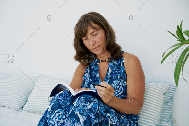 Adult female in blue summer dress sitting on couch and reading interesting book while resting at home
