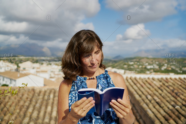 Adult female in summer dress reading book while spending summer day on rooftop of country house