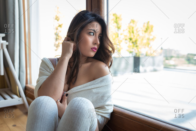 Seductive female with long hair sitting on floor and looking out of window while relaxing at home